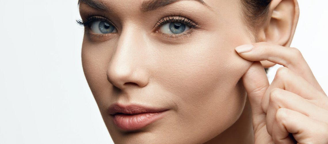Healthy Skin. Beautiful Woman With Beauty Face Pulling Elastic Facial Skin. High Resolution.